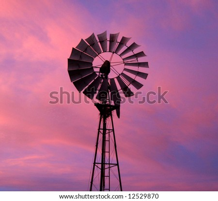 Windmill against dramatic sky covered with purple color. Namibia - stock photo
