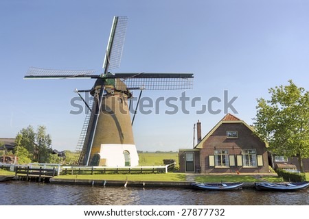 Windmill alongside a river. With next to it the house of the miller.