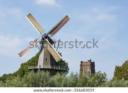 Windmill and church tower in the historical city of Woudrichem in the province of Noord-Brabant, the Netherlands