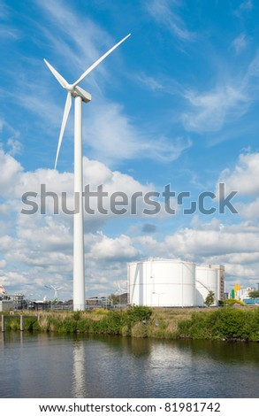 windmill and oil terminal against a cloudy sky in the amsterdam harbor - stock photo