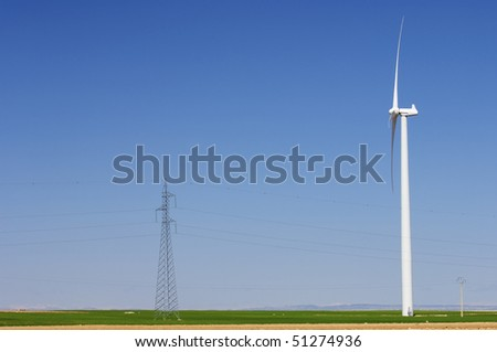 windmill and pylons with clear blue sky - stock photo