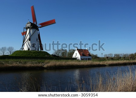 Windmill and small house alongside a canal in Damme, near Bruges, Belgium - stock photo
