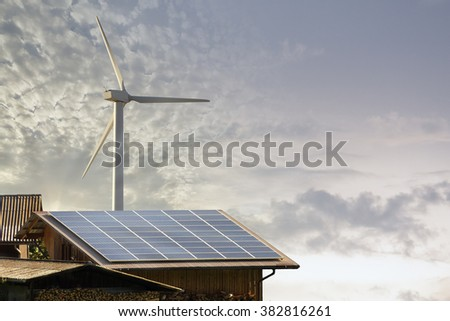 Windmill and solar panel on a roof of an wooden chalet home