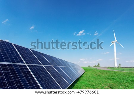 Windmill and solar panels on blue sky at daytime