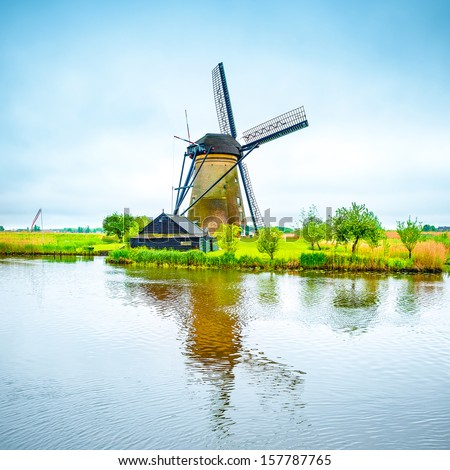 Windmill and water canal reflection in Kinderdijk, Holland or Netherlands. Unesco world heritage site. Europe. - stock photo