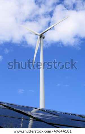 Windmill at front, in background blue sky with some clouds, and in front-bottom of a picture solar panels lie