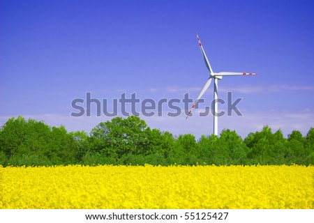 Windmill conceptual image. Windmill on yellow field in summer.