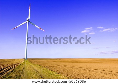 Windmill conceptual image. Windmills on plowed field. - stock photo