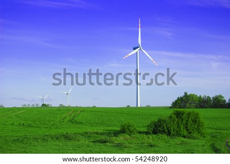 Windmill conceptual image. Windmills on the green field.