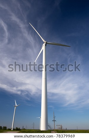 windmill electric power turbine over deep blue sky