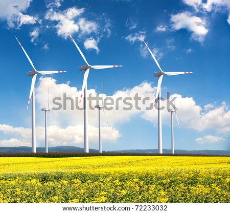 Windmill farm in the rapeseed field - stock photo