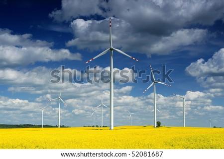 Windmill farm on the rapeseed field - stock photo