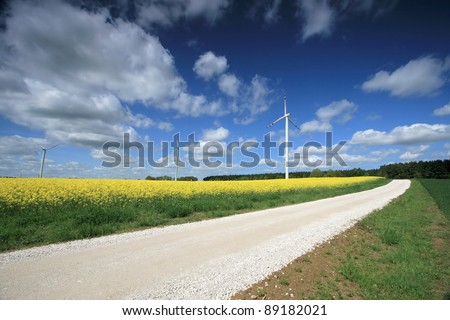 Windmill farm on the rapeseed field - stock photo