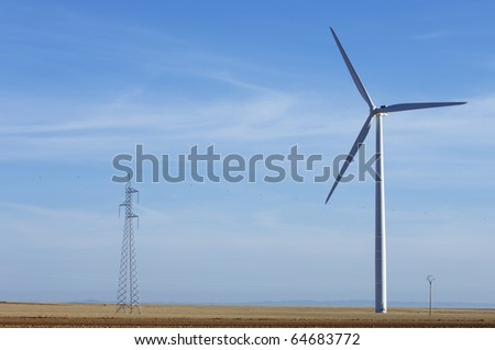 windmill for electric power production and high-tension tower - stock photo