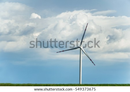 windmill for electric power production on rural floral field under the blue cloudy sky