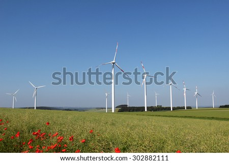 Windmill generator in wide yard / Yard of windmill power generatorunder blue sky, shown as energy industry concept. - stock photo