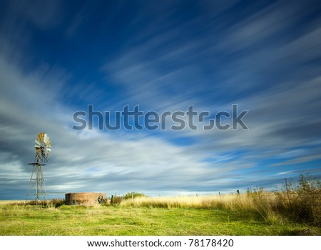 windmill in field with motion in the clouds - stock photo