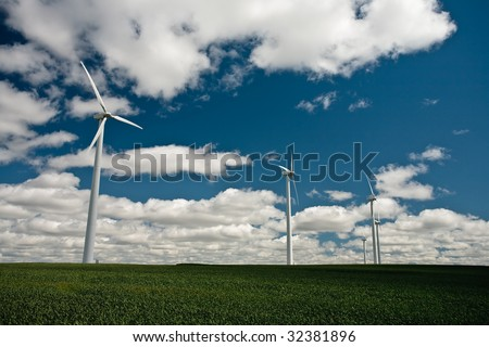 Windmill in green field with white puffy clouds against a blue sky.