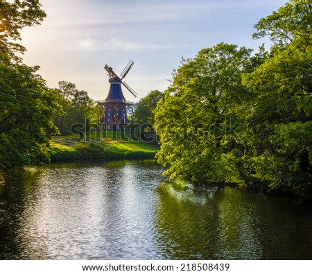 Windmill in river park - stock photo