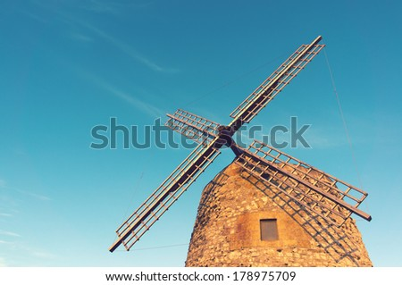windmill in spain with vintage effect against blue sky - stock photo