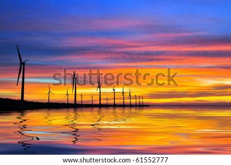 windmill in sunset at seacoast - stock photo