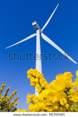 Windmill in the meadow over blue sky - stock photo