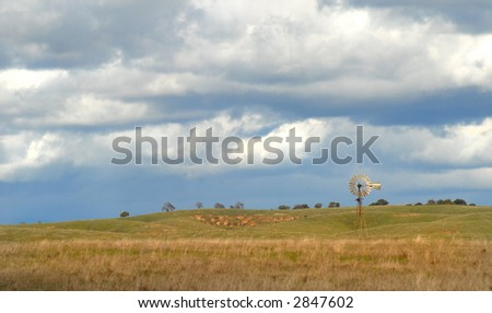 Windmill on a California hillside under a cloud filled sky - stock photo