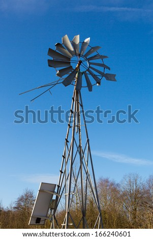 Windmill on a farm in France with a clear and blue sky in the background