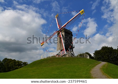 Windmill on a grassy hill in Bruges, Belgium - stock photo