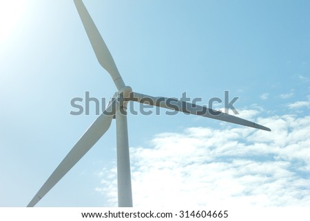windmill on blue sky. can be used for windmills, energy, nature, climate and environment themes - stock photo