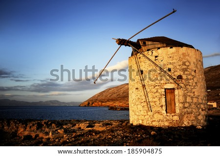 Windmill on sunset in a Greek island - stock photo