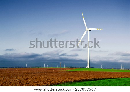 Windmill on the field. Alternative energy. - stock photo