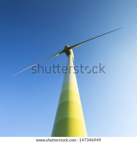 windmill Pinwheel wind turbine wind farm forwards blue skies - stock photo