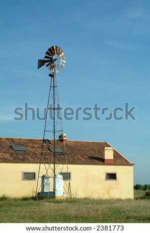 Windmill pump and barn against the sky in farm - stock photo