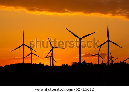 Windmill silhouette on suset background - stock photo