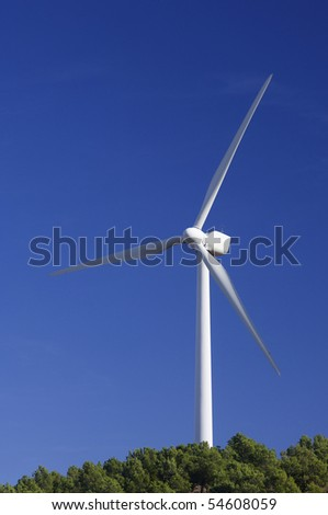 windmill stands in a pine forest, a day of clear blue sky - stock photo