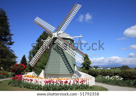 Windmill surrounded by colorful tulips - stock photo