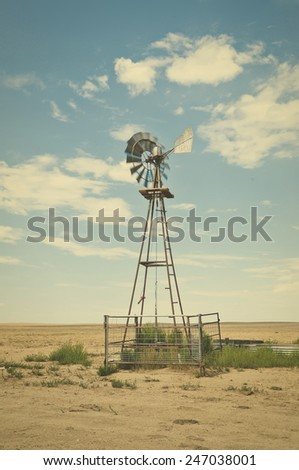 Windmill water pump to supply livestock with drinking water. Retro instagram look. - stock photo