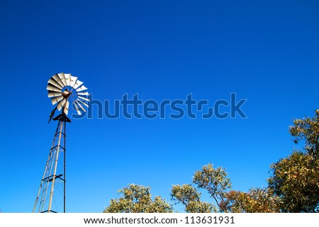 Windmill with blue sky and bush - stock photo