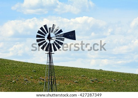 Windmill with cloud filled skies on the open range. - stock photo