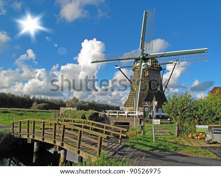 Windmill with wooden bridge in beautiful weather, Netherlands, Europe. - stock photo