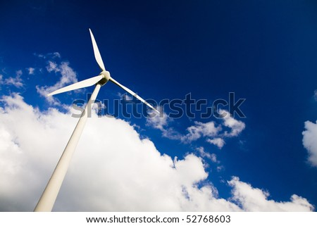 Windmills against a blue sky and clouds, alternative energy source, in horizontal frame