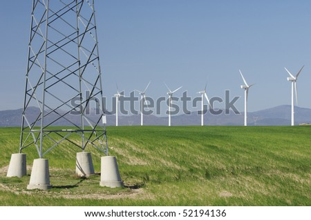 windmills aligned and high voltage electrical line with a clear blue sky - stock photo