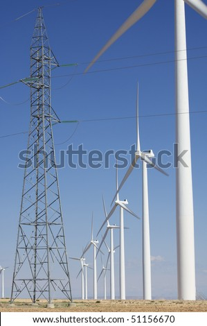 windmills aligned and pylon with a clear blue sky - stock photo