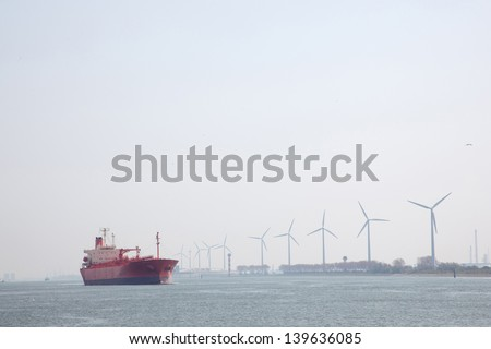 windmills and oil tanker in Nieuwe Waterweg near port of Rotterdam in The Netherlands - stock photo