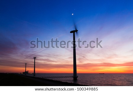 Windmills and plant at sunset with the moon