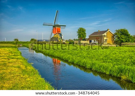Windmills and water canal in Kinderdijk, Holland or Netherlands. Unesco world heritage site. Europe. HDR - stock photo