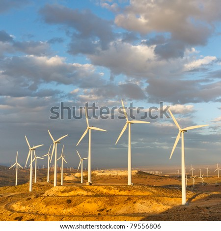 Windmills at Tehachapi Pass Wind Farm, California, generating clean renewable electrical energy without carbon dioxide emissions to fight climate change and global warming. - stock photo