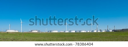 windmills between large white tanks for petrol and oil in the Rotterdam harbor - stock photo