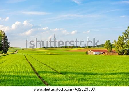 Windmills, eco power, wind turbines on farmland - stock photo